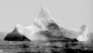 Photograph of iceberg taken by chief steward of Prinz Adalbert on morning of 15 April 1912 near where Titanic sank. At the time he had not learned of the Titanic disaster. Smears of red paint along the base caught his attention. The photo and accompanying statement were sent to Titanic's lawyers, which hung in their boardroom until the firm dissolved in 2002. Public Domain